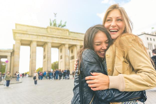 Filles heureuses rencontrant et embrassant à berlin Photo Premium