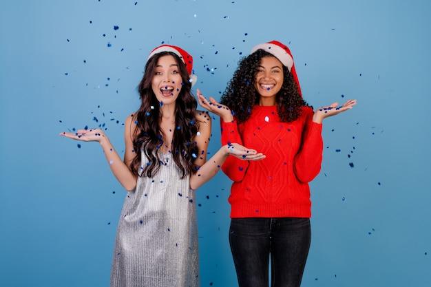 Filles Heureux Avec Des Confettis Dans L'air Portant Des Chapeaux De Noël Isolés Sur Bleu Photo Premium