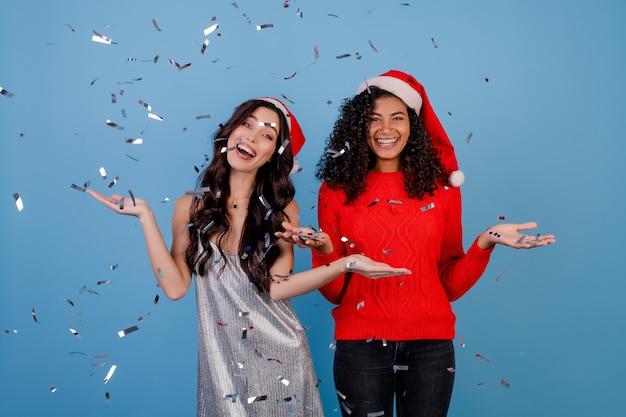 Filles Heureux Avec Des Confettis Dans L'air Portant Des Chapeaux De Santa Photo Premium