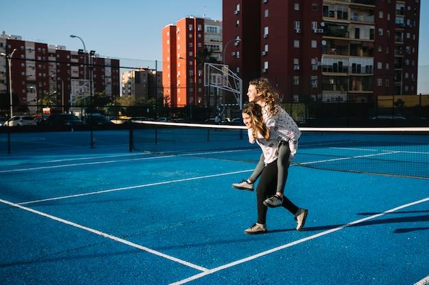 Filles jouant sur le toit avec un terrain de tennis bleu