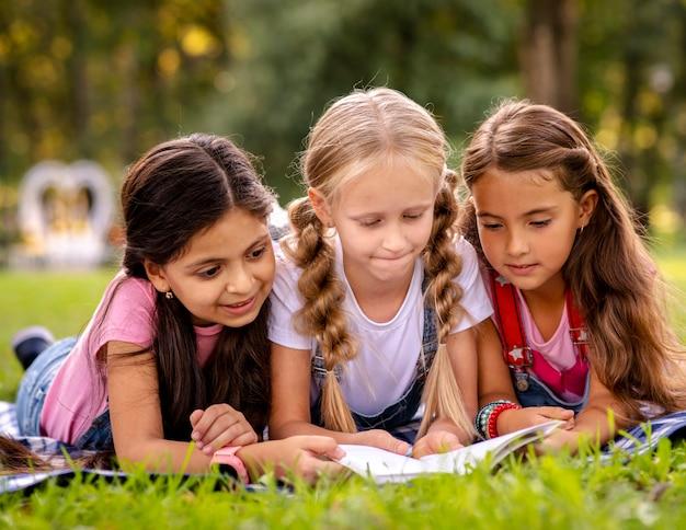 Filles lisant un livre sur l'herbe Photo gratuit