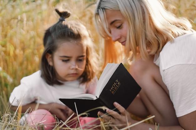 Filles Lisant La Sainte Bible Dans Un Champ De Blé. étudiez Ensemble La Sainte Bible. Photo Premium