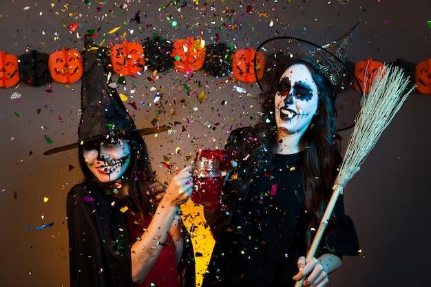 Filles lors d'une fête d'halloween avec confettis Photo gratuit