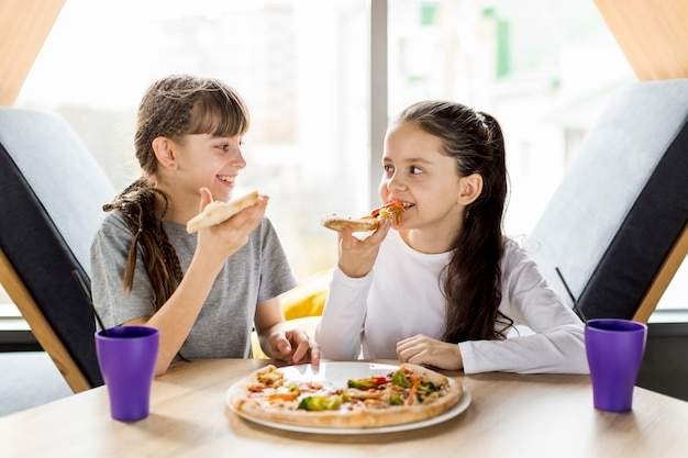 Filles, manger pizza Photo gratuit
