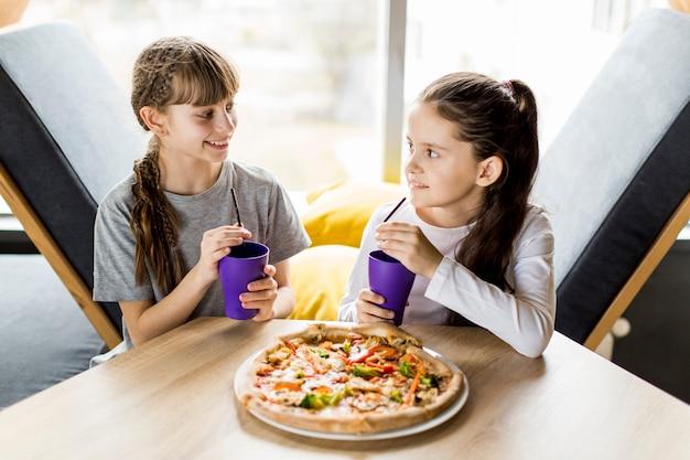 Filles, manger pizza Photo gratuit