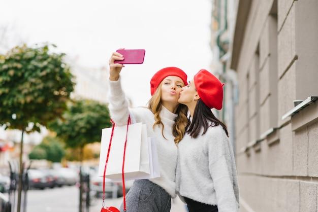 Les Filles Mignonnes Lumineuses Dans Les Bérets Rouges Et Les Chandails Légers Font Un Selfie Au Téléphone Photo Premium