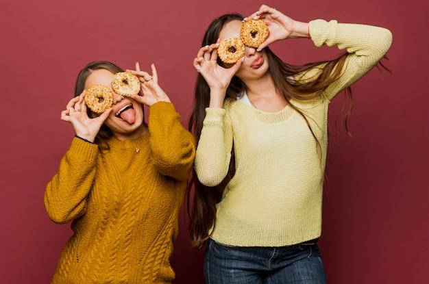 Filles moyen tir avec beignets faire des grimaces Photo gratuit