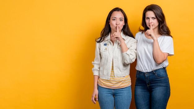 Les filles ont demandé le silence sur fond jaune Photo gratuit