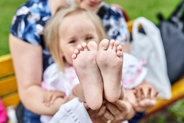Les Filles Pieds Nus Se Bouchent. Maman Change De Chaussures Pour L'enfant Photo Premium