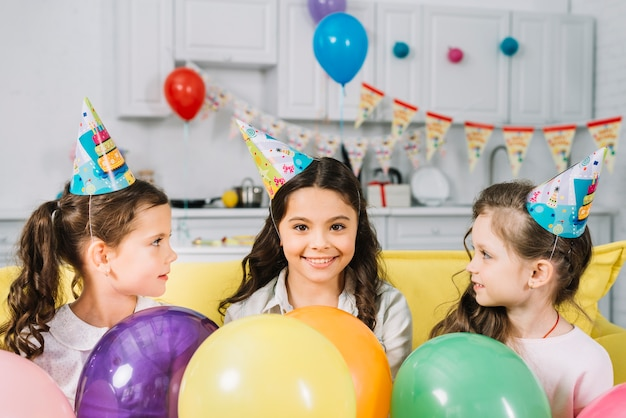 Filles regardant leur ami heureux avec des ballons colorés Photo gratuit