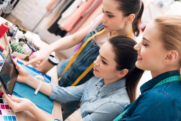 Les filles regardent une tablette dans une fabrique de vêtements. Photo Premium