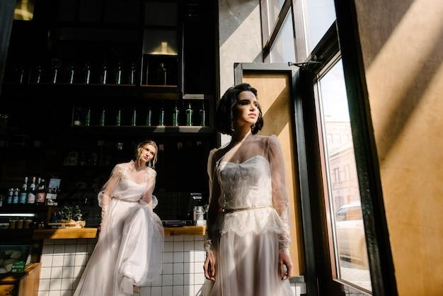 Des filles en robes de mariée blanches posent. Photo Premium