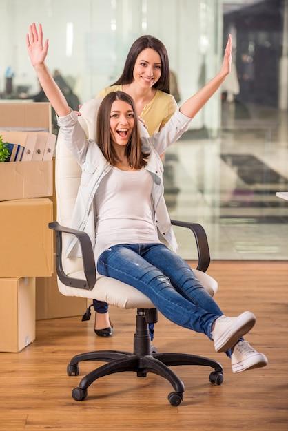 Les filles s'amusent au bureau sur une chaise. Photo Premium