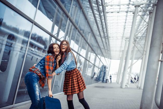 Les filles s'amusent et sont heureuses lorsqu'elles se rencontrent à l'aéroport. Photo Premium