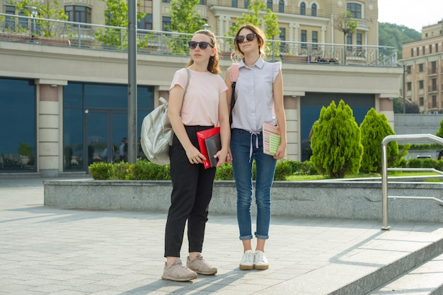 Des filles avec des sacs à dos et des livres vont à l'école Photo Premium