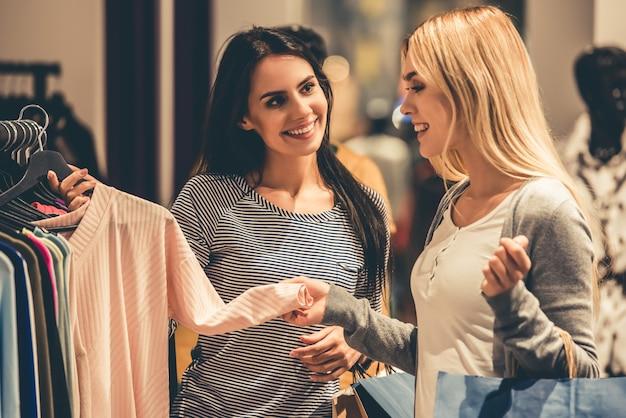Les Filles Avec Des Sacs à Provisions Choisissent Des Vêtements Photo Premium