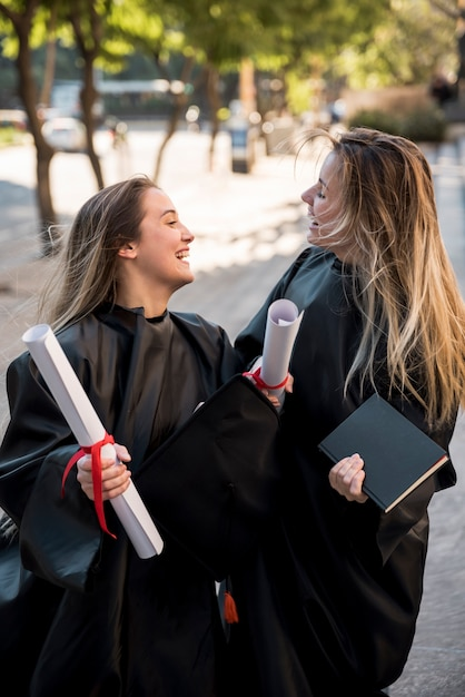 Filles de tir moyen étant gai à leur remise des diplômes Photo gratuit