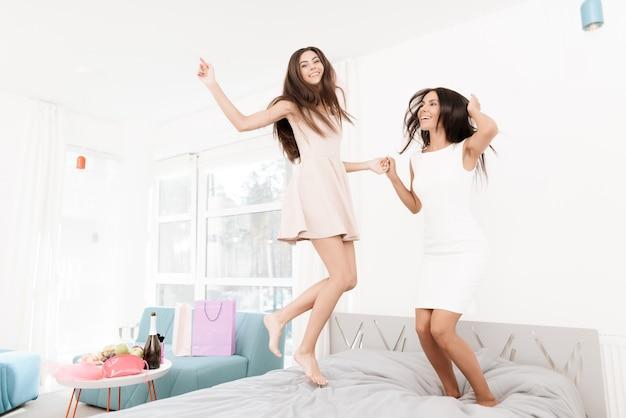 Des filles voilées sautent sur le lit. Photo Premium