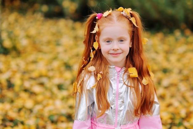 Fillette aux cheveux avec des feuilles tombées jaunes sur ses cheveux en souriant contre les feuilles de l'automne dans le parc. Photo Premium