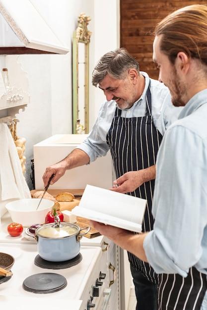 Fils aidant père en cuisine Photo gratuit