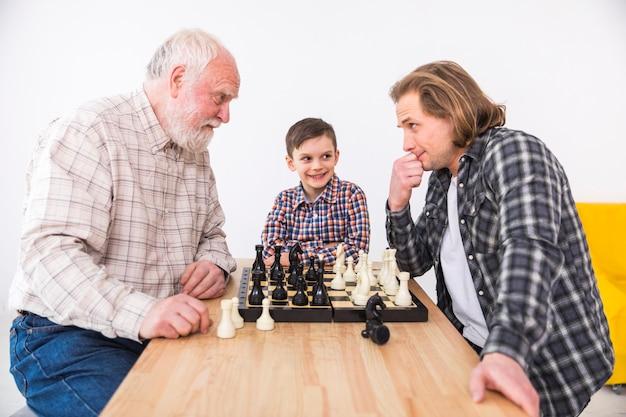 Fils cherche père et grand-père jouant aux échecs Photo gratuit