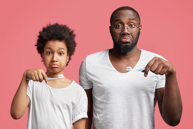 Fils Et Père Afro-américain Tenant Des Brosses à Dents Photo gratuit