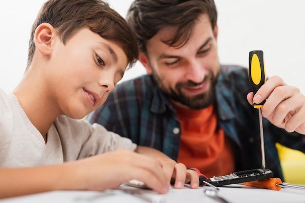 Fils et père réparant un téléphone Photo gratuit