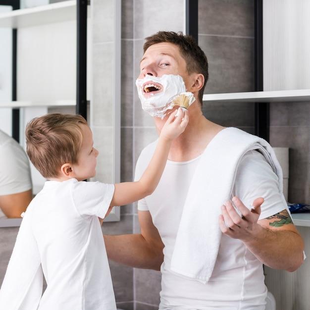 Fils rasant les joues et le menton de son père dans la salle de bain Photo gratuit