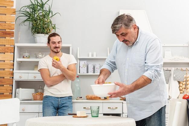 Fils regardant père préparant le dîner Photo gratuit