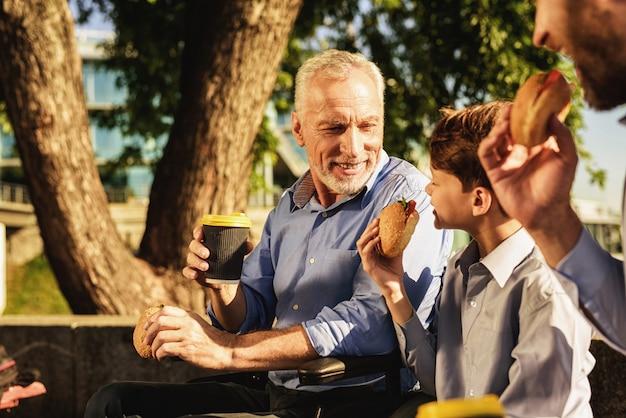 Un fils de la réunion familiale et son petit-fils assis sur un banc Photo Premium