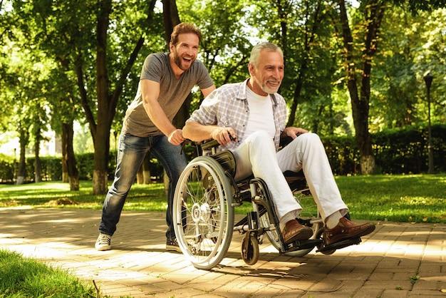 Fils et vieil homme s'amusent. famille marchant dans le parc. Photo Premium