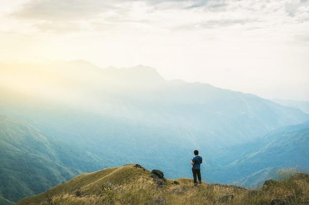 Filtre instagram jeune homme un touriste asiatique en montagne veille sur le lever du soleil brumeux et brumeux Photo Premium