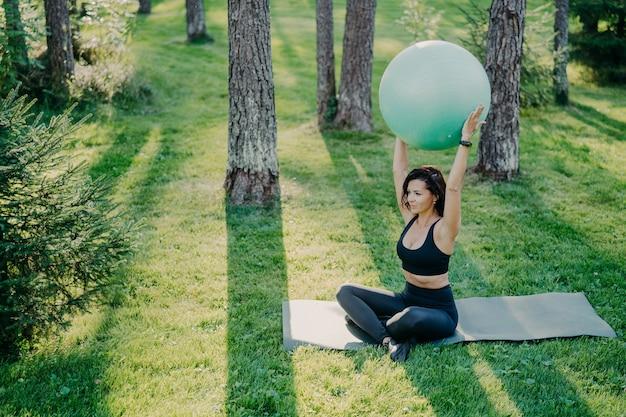 Fit Des Exercices De Femme Sportive Avec Ballon De Fitness Est Assis Sur Un Tapis En Posture De Lotus Photo Premium