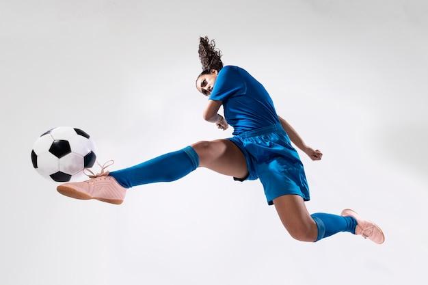 Fit femme adulte jouant au football Photo gratuit