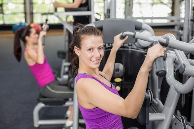 Fit femme à l'aide d'une machine de musculation en salle de sport Photo Premium