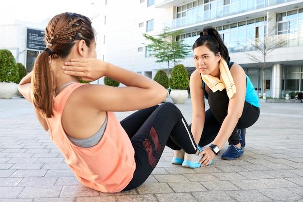 Fit femme asiatique faisant des sit-ups sur le trottoir dans la rue et ami tenant ses pieds Photo gratuit