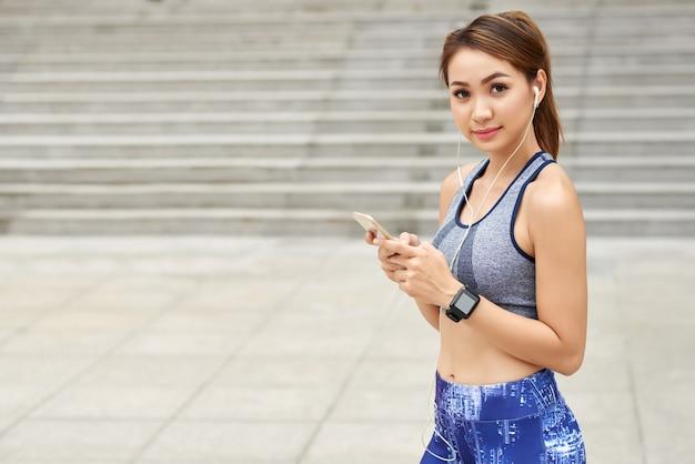 Fit femme asiatique sportswear, avec écouteurs et smartphone posant dans la rue Photo gratuit