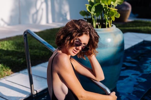 Fit Femme Brune Bronzée En Maillot De Bain Ajusté Noir à L'hôtel Villa Dans La Piscine Photo gratuit