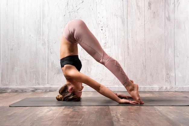 Fit femme exerçant une posture de yoga sirsasana Photo Premium