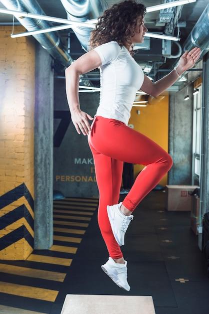 Fit femme faisant de l'exercice sur une boîte en bois dans la salle de sport Photo gratuit