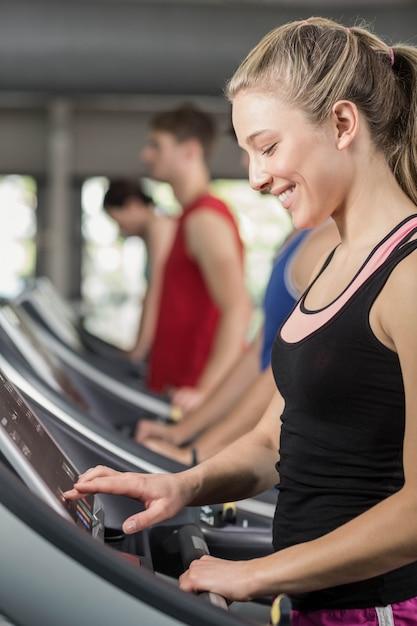 Fit femme qui court sur tapis roulant à la gym Photo Premium