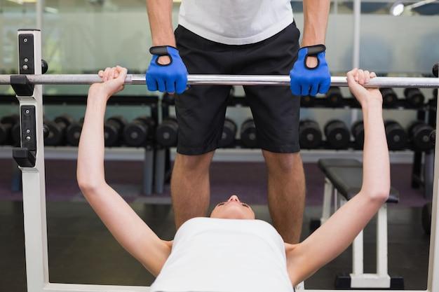 Fit femme soulevant des haltères avec son entraîneur spotting à la salle de gym Photo Premium