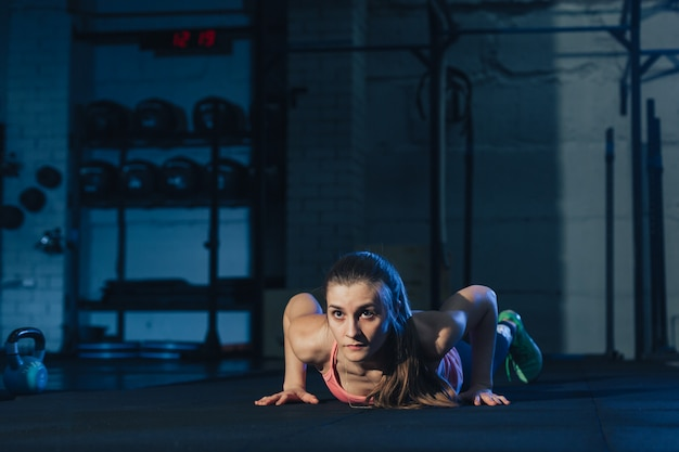 Fit femme en sportswear coloré rose faisant des burpees sur un tapis d'exercice violet dans un espace de type industriel grungy Photo Premium