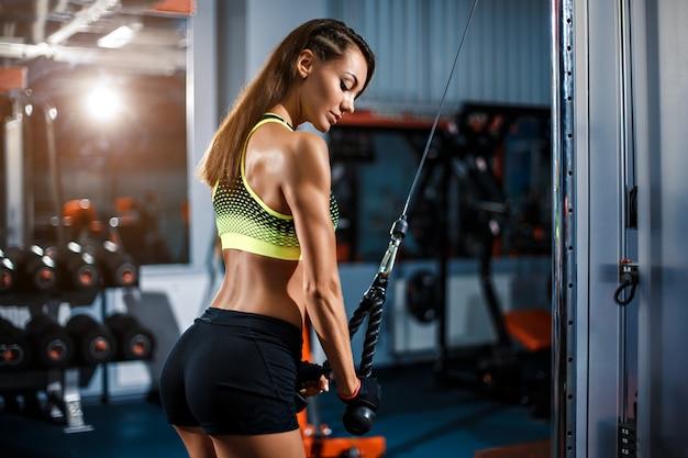 Fit femme triceps d'entraînement soulever des poids dans la salle de gym Photo Premium