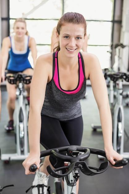 Fit groupe de personnes qui utilisent un vélo d'exercice dans la salle de gym Photo Premium