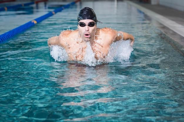 Fit homme nageant dans la piscine Photo Premium