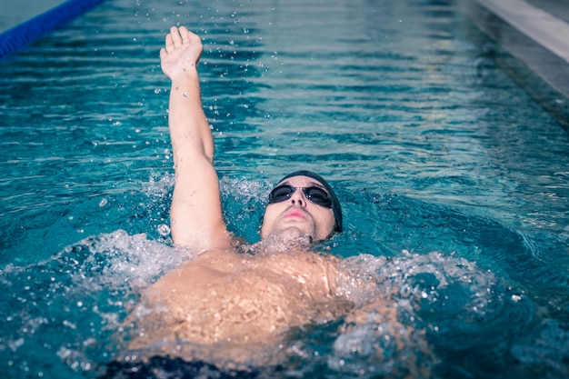 Fit homme nageant sur le dos dans la piscine Photo Premium
