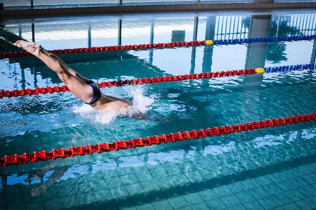 Fit homme plonger dans la piscine Photo Premium