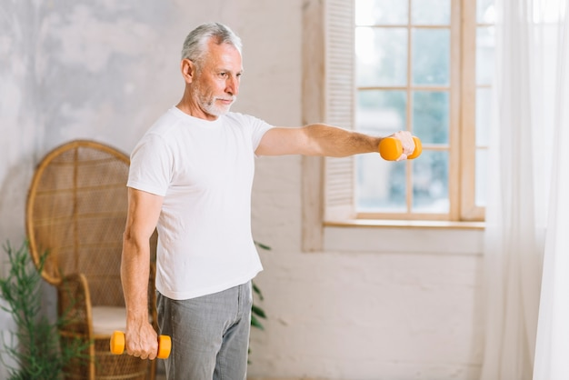 Fit homme senior exerçant avec un haltère orange à la maison Photo gratuit