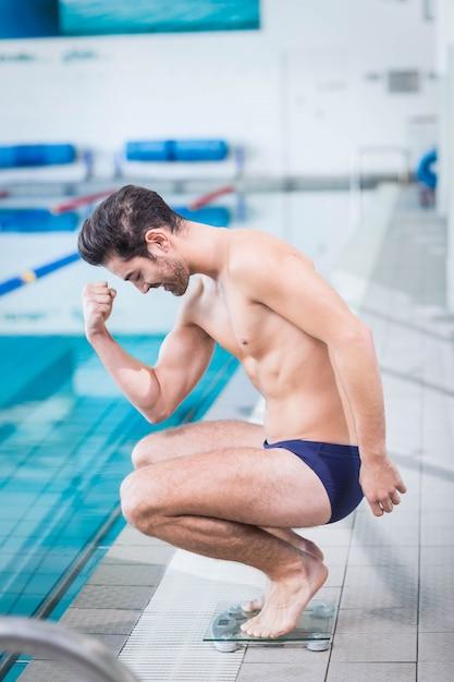 Fit Homme Triomphant Sur La Balance à La Piscine Photo Premium